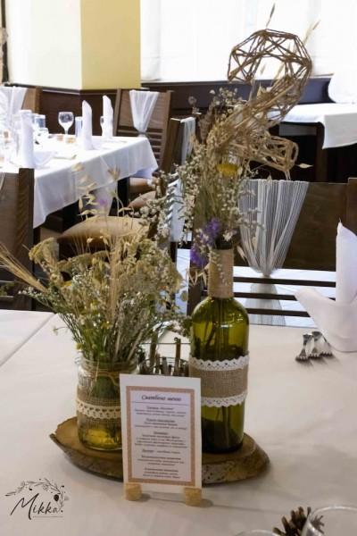 Аранжировка за маса за рустик сватба с дървено пънче, ваза със полски цветя и свещник