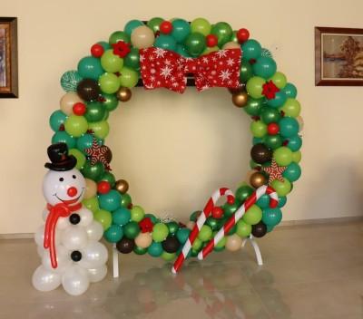 Коледна арка от балони във формата на венец с играчки и панделка и снежен човек от балони