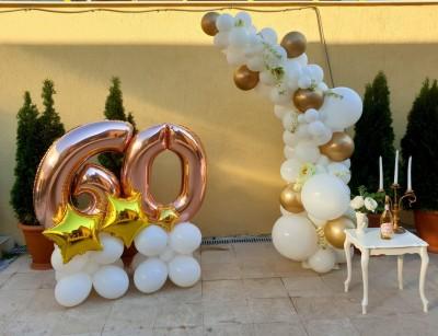 Полуарка в бяло със златни хром балони и цветя за декорация на юбилей