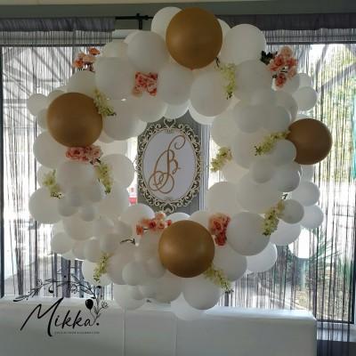 Малка кръгла арка от балони в бяло и златно с цветя