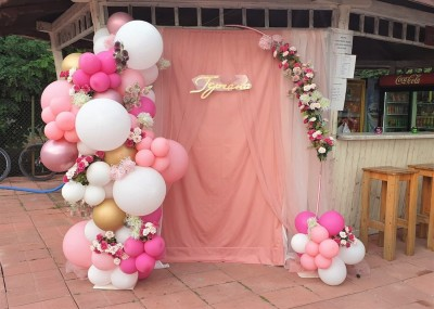 Фотокът с полуарка от балони и цветя в цикламено, бяло и розово